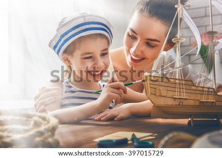 Mother and her child girl making model ship. Dreams of sea, adventures and travel. - stock photo