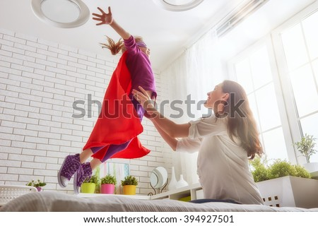 Mother and her child girl playing together. Girl in an Superhero's costume. The child having fun and jumping on the bed. - stock photo