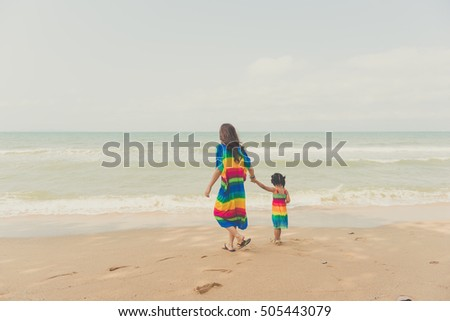 Mother and her child is walking at the beach.