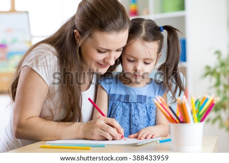 mother and her child pencil together - stock photo