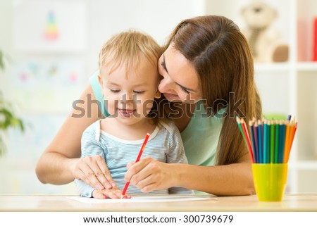 mother and her child pencil together at home - stock photo