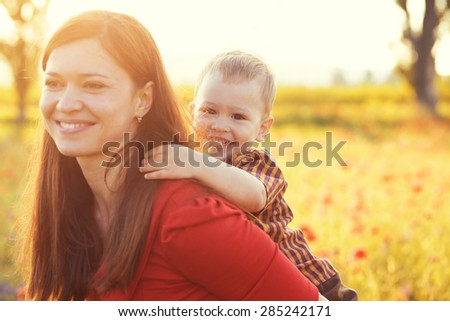Mother and her child playing in spring poppy field in soft sunlight