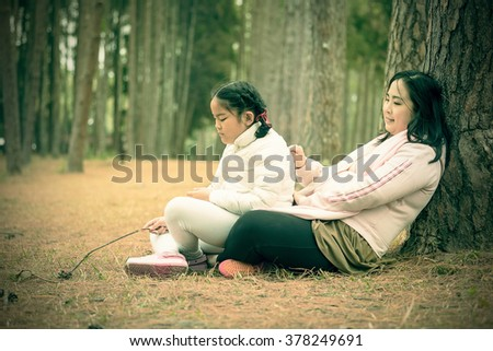 Mother and her child playing in the pine woods - stock photo