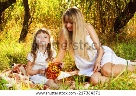 Mother and her child resting outdoors. Holiday