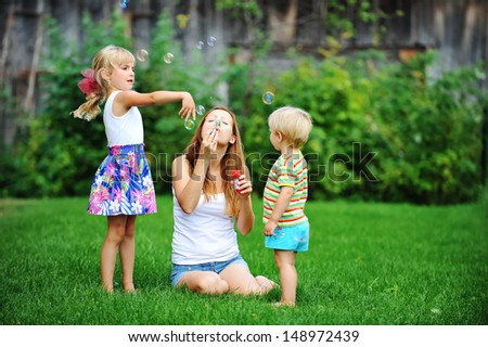 mother and her children play with bubble blower on green lawn - stock photo