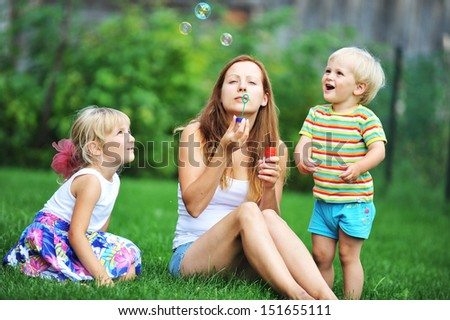 mother and her children play with bubble blower on green lawn