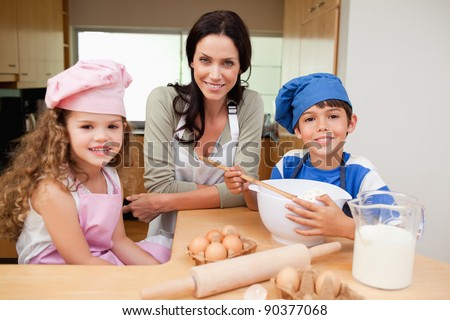 Mother and her children preparing cake together - stock photo