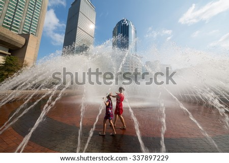 Mother and her daughter are dancing together into the fountain at autumn day. - stock photo