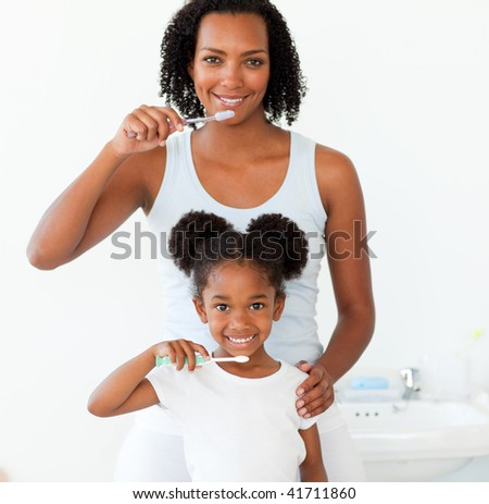 Mother and her daughter brushing their teeth in the bathroom - stock photo