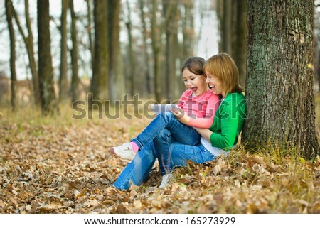 Mother and her daughter is playing with tablet, outdoor shoot - stock photo