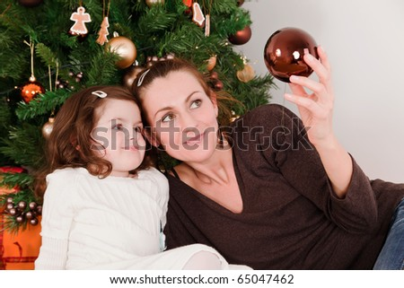 Mother and her daughter looks christmas-tree decoration - stock photo