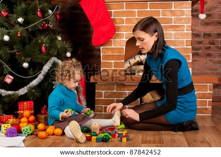 Mother and her daughter near Christmas tree - stock photo