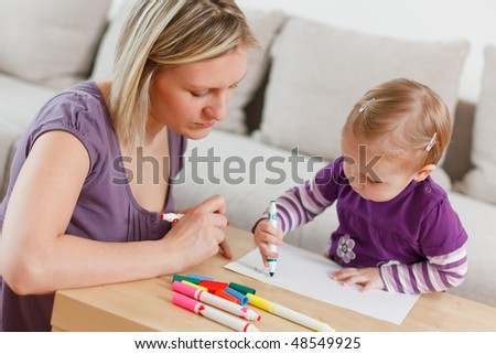 mother and her daughter painting in living room