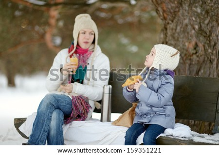 Mother and her daughter picnicking in the park at winter - stock photo