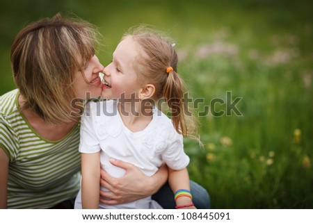 Mother and her daughter playing outdoors nose to nose - stock photo