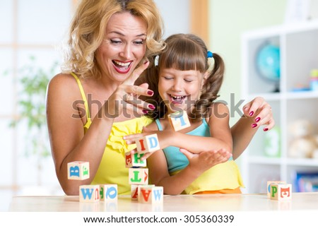Mother and her daughter playing with cubes at home - stock photo
