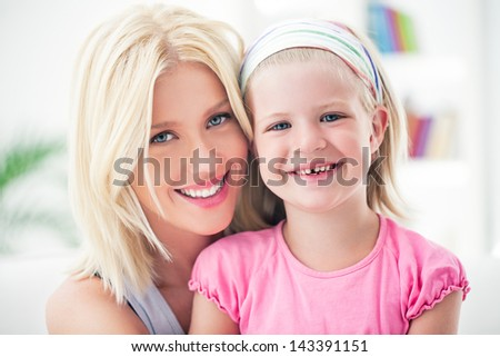 Mother and her daughter posing and smiling. - stock photo
