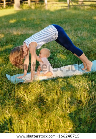 Mother and her daughter practice yoga - stock photo