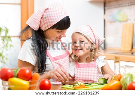mother and her daughter preparing vegetables at kitchen - stock photo