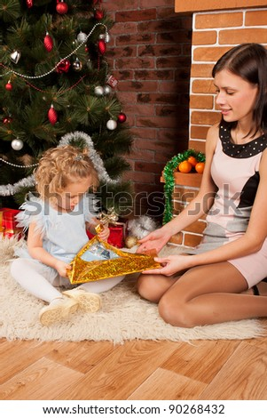 Mother  and her daughter receiving Christmas gifts - stock photo