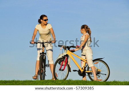 Mother and her daughter riding on a bicycles - stock photo