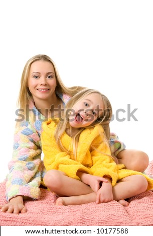 Mother and her daughter sitting on a bed - stock photo