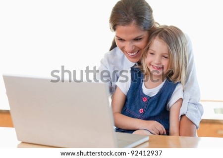 Mother and her daughter using a notebook in their kitchen - stock photo