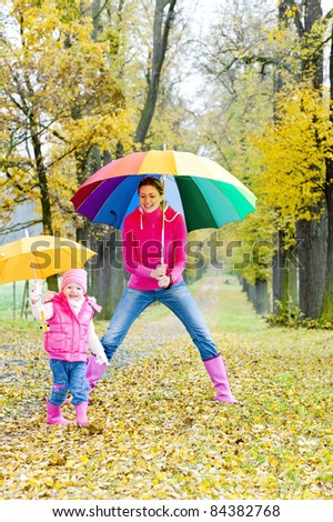 mother and her daughter with umbrellas in autumnal alley - stock photo