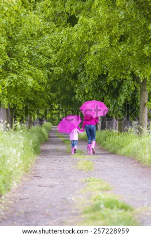 mother and her daughter with umbrellas in spring alley - stock photo