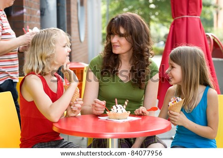 Mother and her daughters in ice cream shop - stock photo