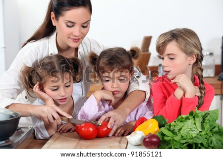 mother and her daughters making salad - stock photo