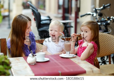 Mother and her daughters relaxing in outdoor restaurant - stock photo
