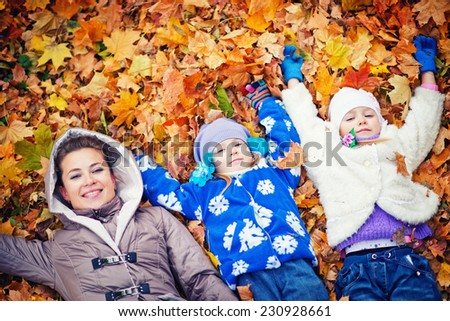 mother and her doughters in autumn park - stock photo
