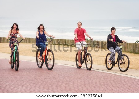 Mother and her fully grown children riding bicycles together - stock photo