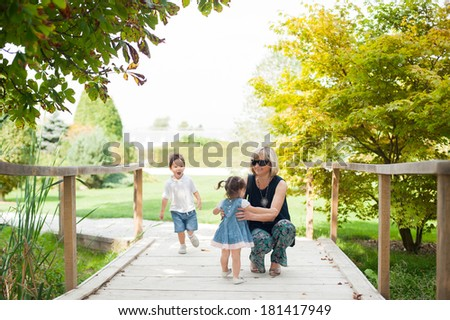 Mother and her grandchildren are having fun in the park - stock photo