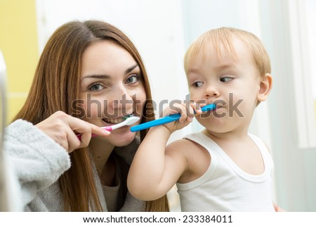 mother and her kid son brushing teeth in bathroom - stock photo