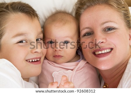 Mother and her kids in the bed, big brother is close to his swaddled sister. All of them smiling happily looking at camera while. - stock photo