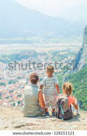 Mother and her kids looking at the town of Kalambaka bird's eye view. Vertical view. Meteora, Greece. - stock photo