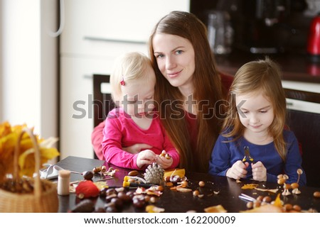 Mother and her kids making chestnuts creatures together - stock photo