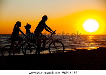 Mother and her kids on the bicycle silhouettes on beach at sunset - stock photo