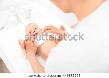Mother and her little baby after bath on changing table