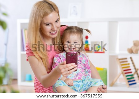 Mother and her  little child girl taking selfie on a blanket in nursery room - stock photo