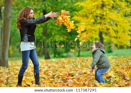 Mother and her little child having fun in a park - stock photo
