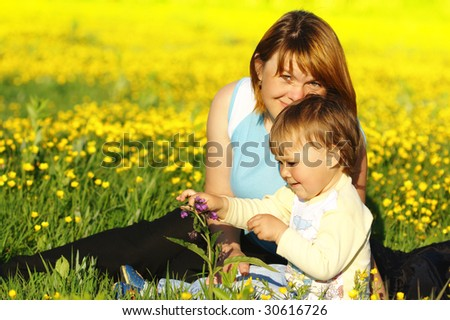 Mother and her little child play on meadow