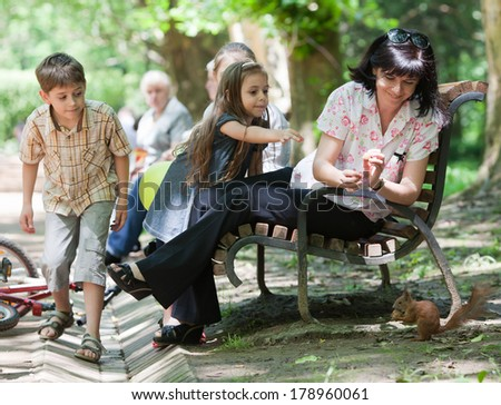 Mother and her little children feeding squirrel in the park at sunny day - stock photo