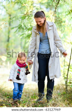 Mother and her little daughter at autumn forest - stock photo