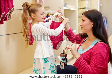 Mother and her little daughter choose swimsuit for girl in clothing store - stock photo