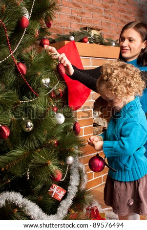 Mother and her  little daughter decorating Christmas tree - stock photo