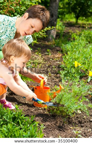 Mother and her little daughter doing gardening - stock photo
