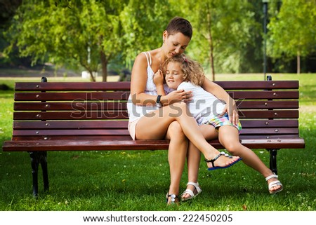 Mother and her little daughter embracing while sitting on a park bench. - stock photo